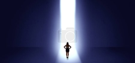 Photo for Woman standing and seeing the light at the end of a big wall - Royalty Free Image