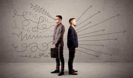 Photo pour Jeune homme d'affaires de choisir entre deux directions avec des flèches et des gribouillis autour de lui en conflit - image libre de droit
