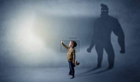 Photo for Cute kid in a room with plush on his hand and hero shadow on his background - Royalty Free Image