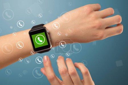 Main avec smartwatch et icône d'appel autour