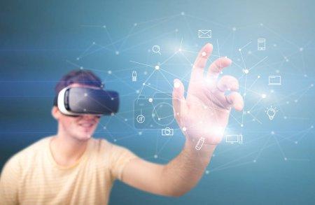 Photo pour Jeune homme impressionné portant des lunettes de réalité virtuelle avec des icônes mixtes autour de son doigt - image libre de droit