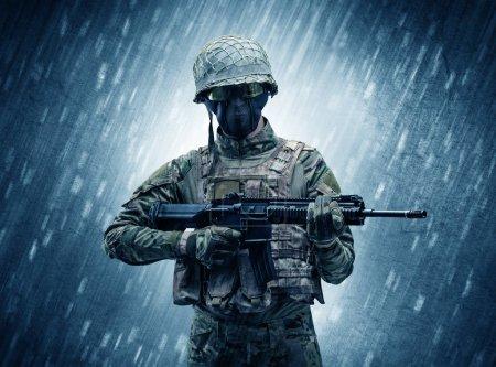 Photo pour Soldat armé debout sous la pluie - image libre de droit