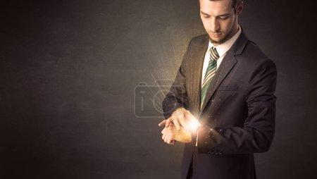 Photo pour Homme d'affaires, porte smartwatch avec brillants rayons sur elle. - image libre de droit