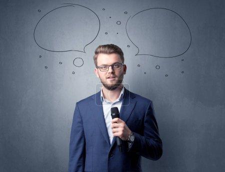 Photo pour Homme d'affaires parlant dans le microphone avec des bulles de parole au-dessus de sa tête - image libre de droit