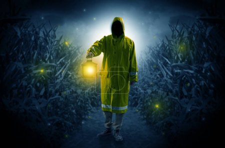 Photo for Man in raincoat at night coming from thicket and looking something with glowing lantern - Royalty Free Image