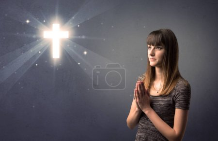 Photo for Young woman praying on a grey background with a shiny cross above her - Royalty Free Image