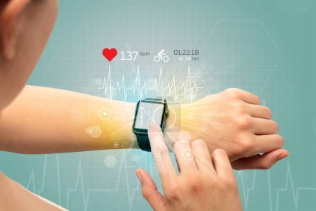 Photo for Hand with smartwatch and cycling concept nearby. - Royalty Free Image