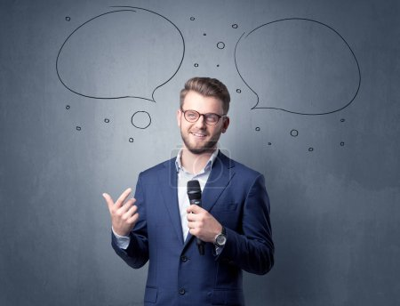 Photo for Businessman speaking into microphone with speech bubbles over his head - Royalty Free Image