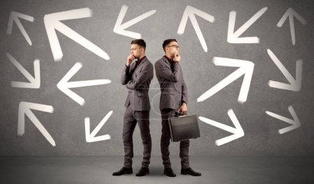 Photo for Young conflicted businessman choosing between two directions with arrows around him - Royalty Free Image
