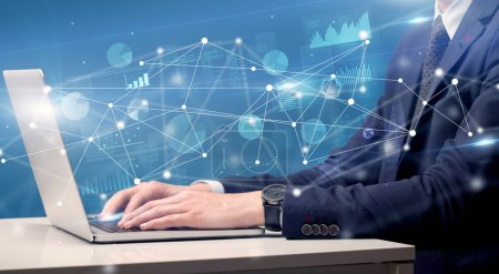 Photo for Businessman typing on laptop with linked reports charts grapghs around - Royalty Free Image
