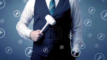 Photo for Young serious businesman holding tool with wrench icons around - Royalty Free Image