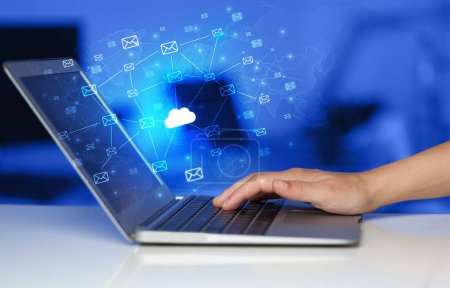Hand mit Laptop mit zentralisiertem Cloud Computing Systemkonzept