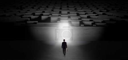 Photo pour Homme d'affaires se préparant à entrer dans le labyrinthe sombre avec porte éclairée - image libre de droit