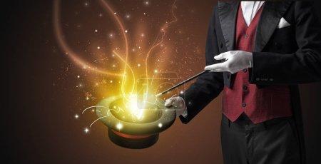 Photo pour Main de magicien évoquer avec la baguette lumineuse d'un cylindre noir - image libre de droit