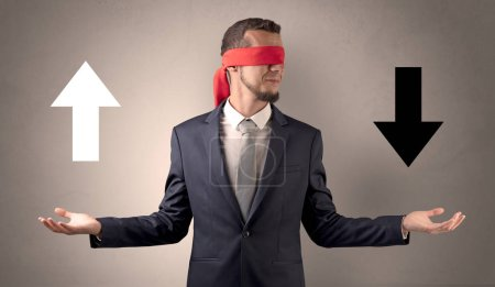 Photo for Covered eye businessman choosing between two directions - Royalty Free Image