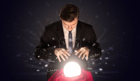 Photo for Gorgeous businessman looking to inspiration in a magic ball in his lap and doodle concept - Royalty Free Image