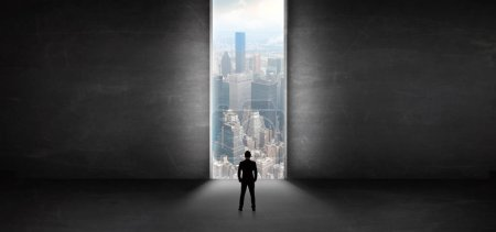 Photo for Businessman standing in a dark room and looking outside to a cityscape view - Royalty Free Image