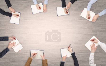 Group of people with devices in hands having desk discussion and working on laptops, tablets in team