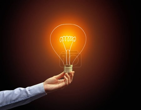 Photo for Hand holding light bulb on dark background, new idea concept - Royalty Free Image