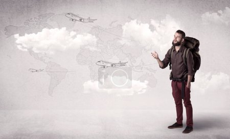 Photo for Handsome young man standing with a backpack on his back and planes in front of a world map as a background - Royalty Free Image