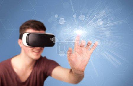 Photo pour Jeune homme impressionné portant des lunettes de réalité virtuelle avec hexagones bleus autour de lui - image libre de droit
