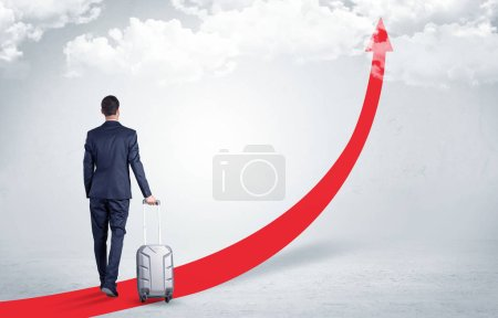 Photo for Young businessman with back leaving on the red arrow carpet to the skies with luggage on his hand - Royalty Free Image