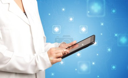Photo for Female doctor holding tablet with blue background and crosses - Royalty Free Image