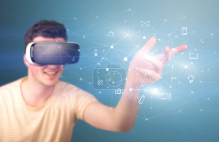 Photo for Young impressed man wearing virtual reality goggles with mixed media icons around his finger - Royalty Free Image