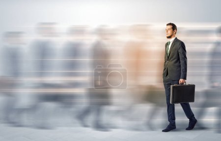 Photo pour Jeune homme d'affaires avec mallette dépêchez-vous dans une rue bondée de gens floues autour - image libre de droit