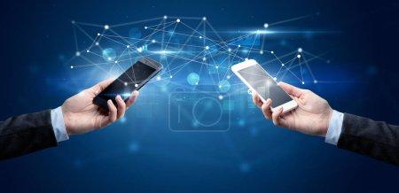 Photo pour Gros plan de deux mains tenant des smartphones et partageant des données professionnelles - image libre de droit