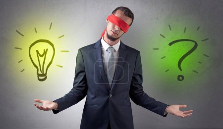 Photo for Covered eye businessman with bulb and question sign symbols around - Royalty Free Image
