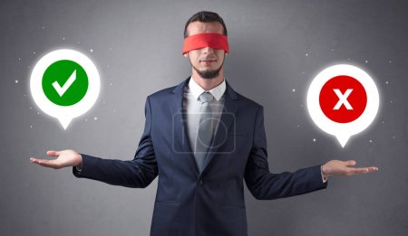 Photo for Blindfolded businessman with checked and x mark above his hand - Royalty Free Image