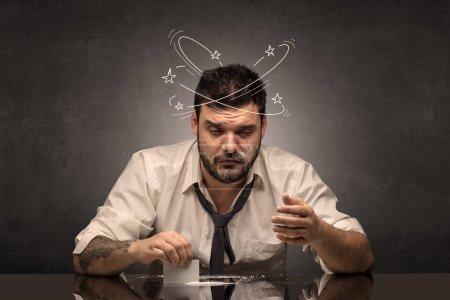 Photo pour Jeune homme ivre à son bureau avec des gribouillis autour - image libre de droit