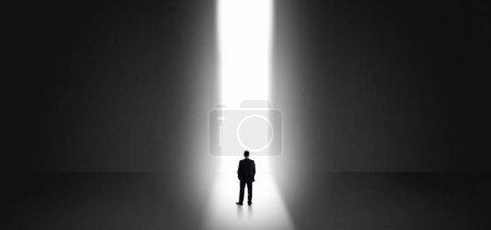 Photo pour Homme d'affaires debout et voyant la lumière au bout d'un grand mur - image libre de droit
