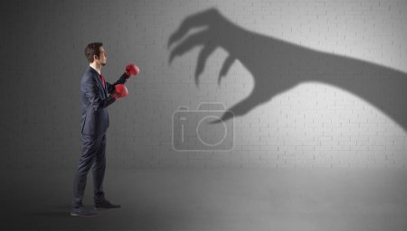 Photo for Tiny businessman fighting with scary hand shadow - Royalty Free Image