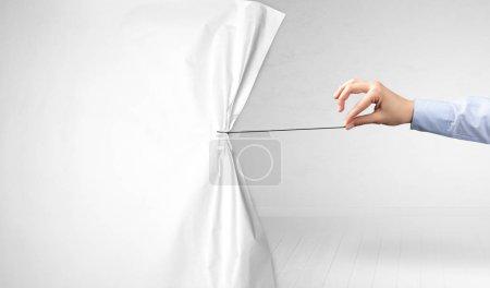 Foto de De la mano tirando de cortina de papel blanco, cambiando el concepto de escena - Imagen libre de derechos