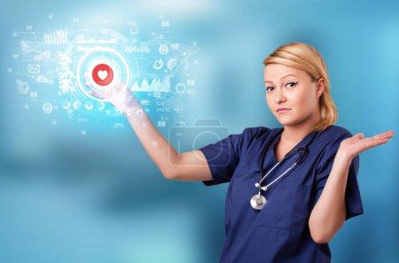 Photo pour Docteur touchant écran hologramme affichant des symboles médicaux et des graphiques - image libre de droit