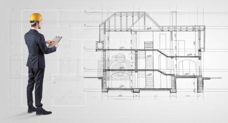 Photo pour Architecte regardant un plan de maison 2 dimensions - image libre de droit