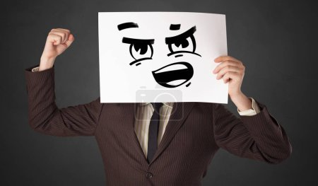 Photo for Casual person holding a paper with funny emoticon in front of her face - Royalty Free Image