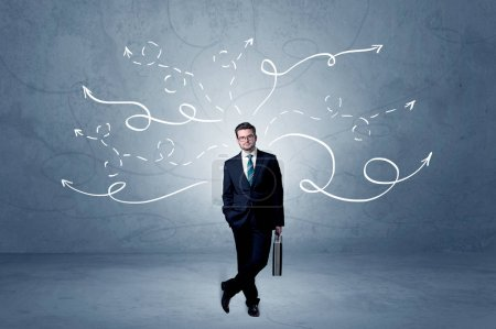 Photo for Elegant businessman choosing between directions with winding drawn arrows around - Royalty Free Image