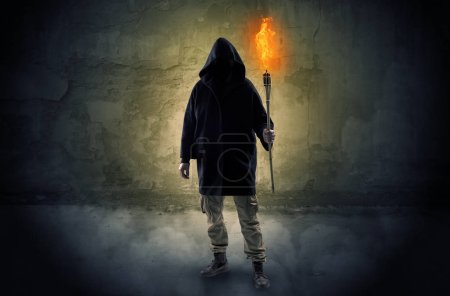 Photo for Ugly wayfarer with burning torch in his hand in front of a crumbly wall concept - Royalty Free Image