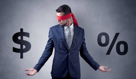 Photo for Serious businessmen standing in front of a grey wall with red ribbon on his eye, holding dollars - Royalty Free Image