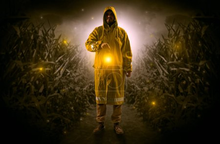 Man in raincoat at night coming from thicket and l...