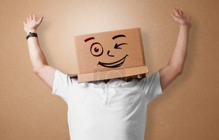 Photo pour Beau homme debout et gesticulant avec une boîte en carton sur la tête - image libre de droit