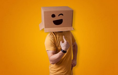 Photo pour Homme drôle portant boîte en carton sur sa tête avec le visage souriant - image libre de droit
