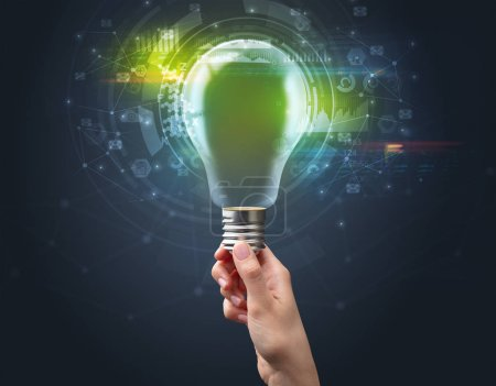 Photo for Hand holding light bulb on dark background. New business idea concept - Royalty Free Image