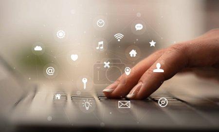 Photo pour Femme d'affaires tapant à la main sur le clavier avec des icônes d'application autour - image libre de droit
