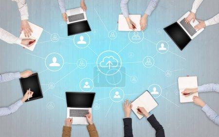 Photo pour Groupe de personnes avec des appareils dans les mains travaillant en équipe sur tablettes, ordinateurs portables avec bureau, connexion, concept cloud - image libre de droit