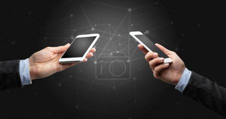 Photo pour Gros plan de deux mains tenant les smartphones les uns aux autres, concept de connexion sans fil - image libre de droit