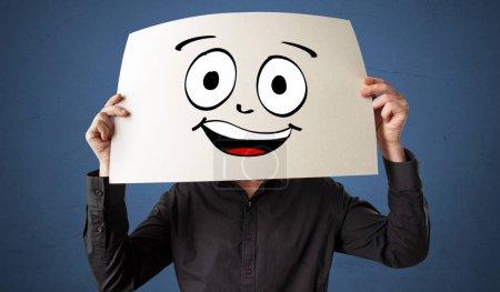 Photo pour Jeune étudiant tenant un papier avec l'émoticône riant devant son visage - image libre de droit